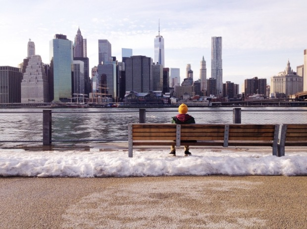 person sitting on bench looking across river at NYC skyline