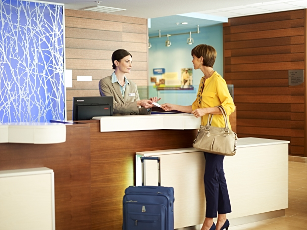 woman with luggage checking in to hotel