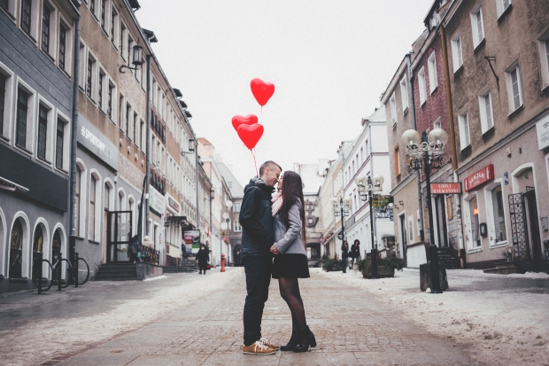 couple kissing in the street with heart-shaped balloons