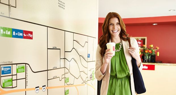 woman with coffee next to map