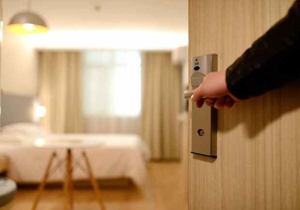 a hand opening a hotel guest room door